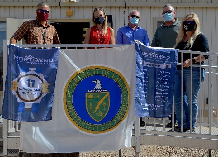 Officials with the Moab Uranium Mill Tailings Remedial Action Project hold up commemorative flags recognizing the milestone of disposing 11 million tons of mill tailings.