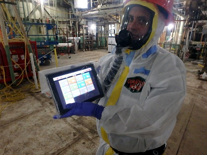 A worker shows a safety app on his tablet screen that displays real-time heat indexes, heart rates, and hourly forecasts specific to the user's location. Supervisors can track their team members' health simultaneously using the tool.