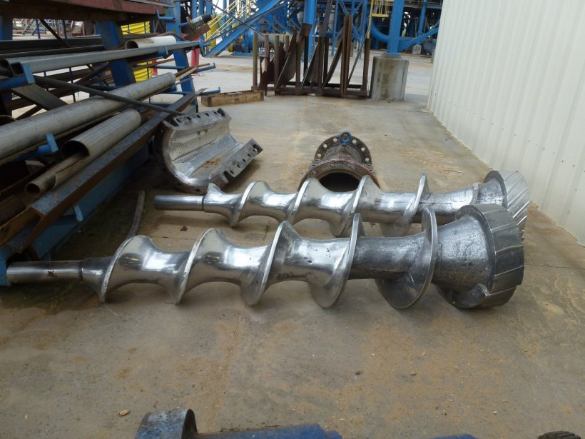 Two screw augers, one new (foreground) and one eroded (background), which was pulled from the machinery for rebuilding