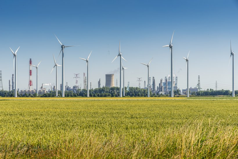 Skyline with nuclear and renewable energy sources and a grain field in the foreground, shot with a clear blue sky.