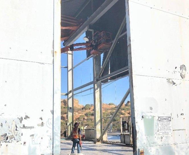Crews remove asbestos siding at Building 4022 at the Energy Technology Engineering Center's Radioactive Materials Handling Facility.