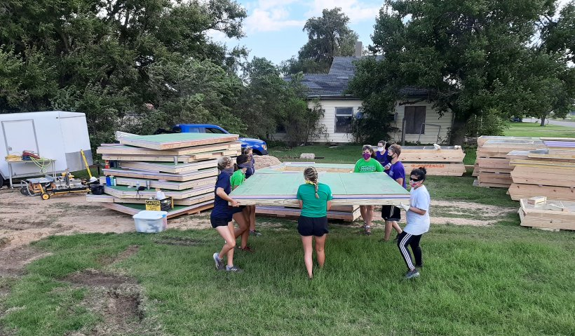 Kansas State University students competing in the Solar Decathlon Build Challenge move completed panels at the building site.