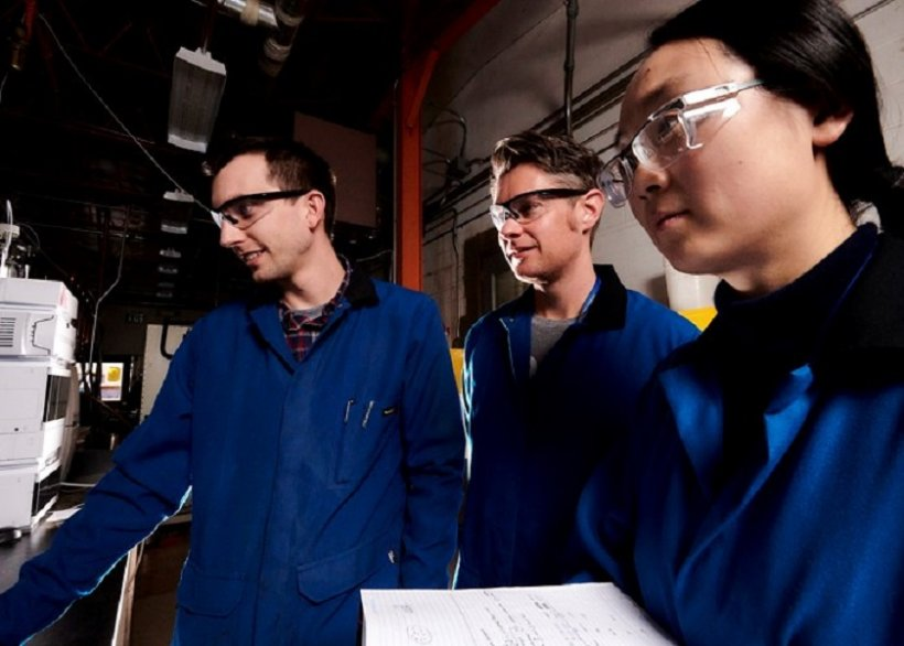 a photo of 3 researchers in a lab