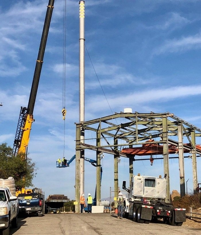 A crew tears down a stack attached to Building 4022 at the Radioactive Materials Handling Facility (RMHF) at the Energy Technology Engineering Center. Teardown of the structure marked the completion of demolition of a set of 10 buildings at the RMHF.