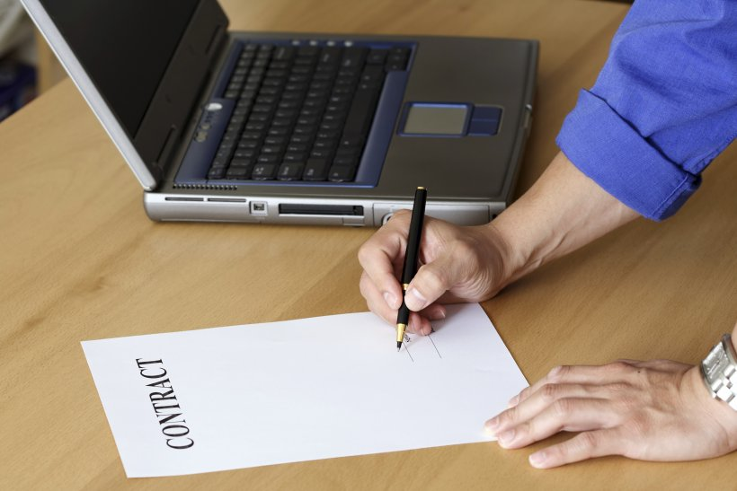 Person writing a contract with a computer.