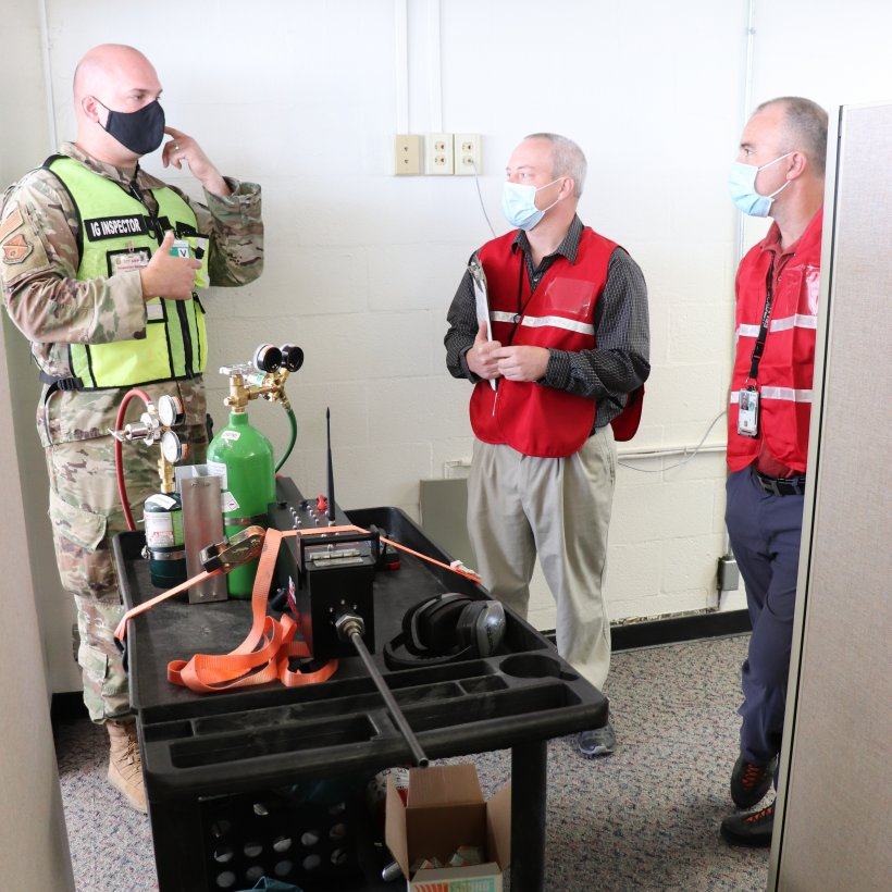 """NNSA Albuquerque Complex Management Team employees Kevin McElvany and Timothy """"Ozzy"""" Oswald confer with the operator of the gun simulator machine used during the exercise."""