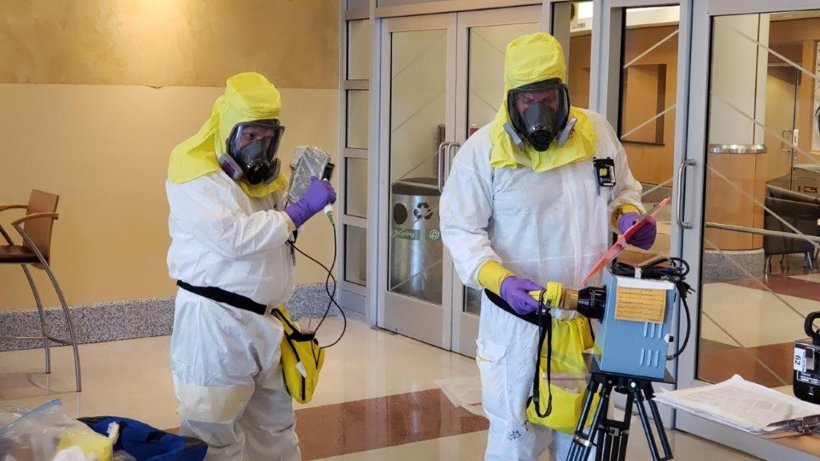 Experts in protective gear prepare to sweep the University of Washington's Research and Training Building for cesium contamination.