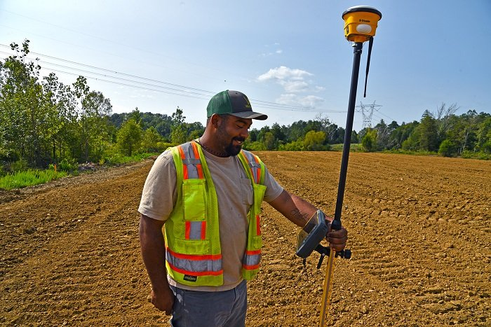 An EM worker relies on a handheld device with GPS technology to ensure precise soil coverage over the various contours of a former oil tank farm site at Oak Ridge.