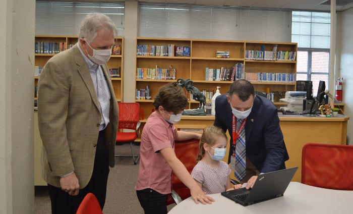 UCOR President and CEO Ken Rueter, left, and Kirk Renegar, an Oak Ridge School District principal, watch as local students use one of 100 new laptops the contractor donated to support virtual learning.