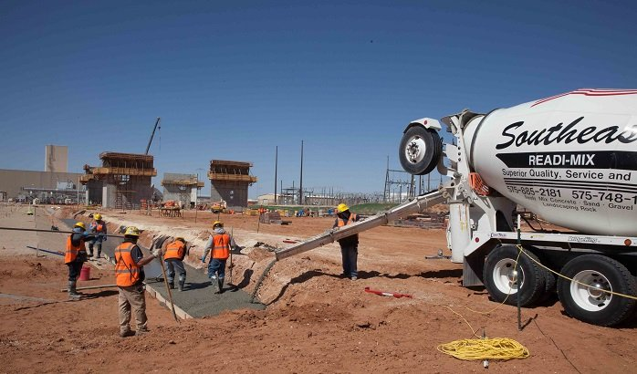 Workers pour concrete for what is known as a mud mat at the Safety Significant Confinement Ventilation System's New Filter Building. The concrete mat will be used to place the building slab on grade formwork. The 55,000-square-foot building's filters will be the final stop for air exhausted from the Waste Isolation Pilot Plant underground repository.