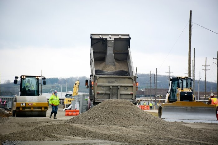 Crews deliver a load of dirt near the X-326 building as work continued on haul road construction.