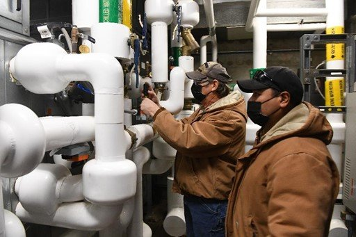 Instrument technicians adjusting hot water controls in an equipment room at the Pantex Plant.