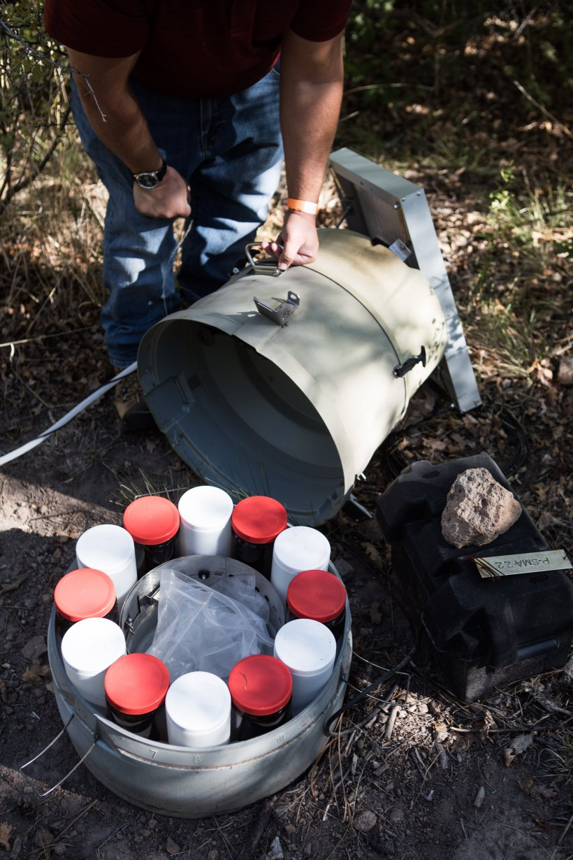A stormwater sampling station in Pueblo Canyon is inspected by an environmental professional.