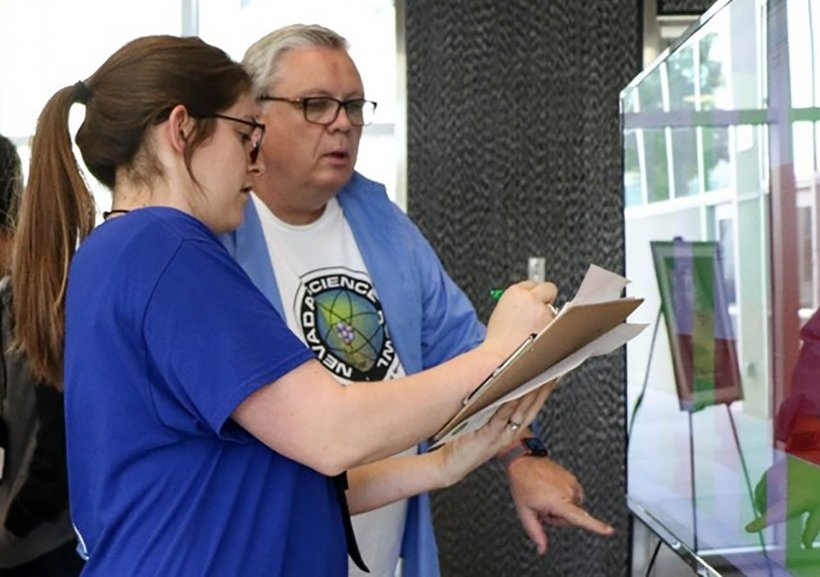 Darwin Morgan working alongside NNSS's Kayla Buchanan during the Nevada Science Bowl in February 2018.