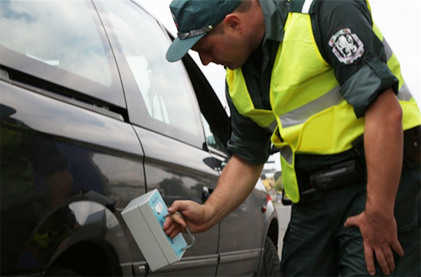 A front-line officer in Bulgaria performs a vehicle inspection with a portable radiation detection system.