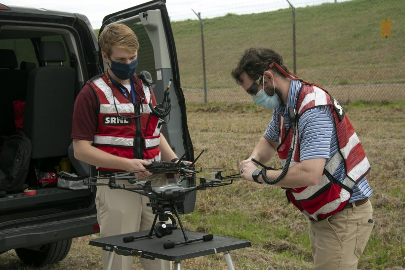 Savannah River National Laboratory employees Dalton Hare, left, and Jeff Steedley prepare a drone for flight to inspect engineered protective covers at remediated waste sites at the Savannah River Site.