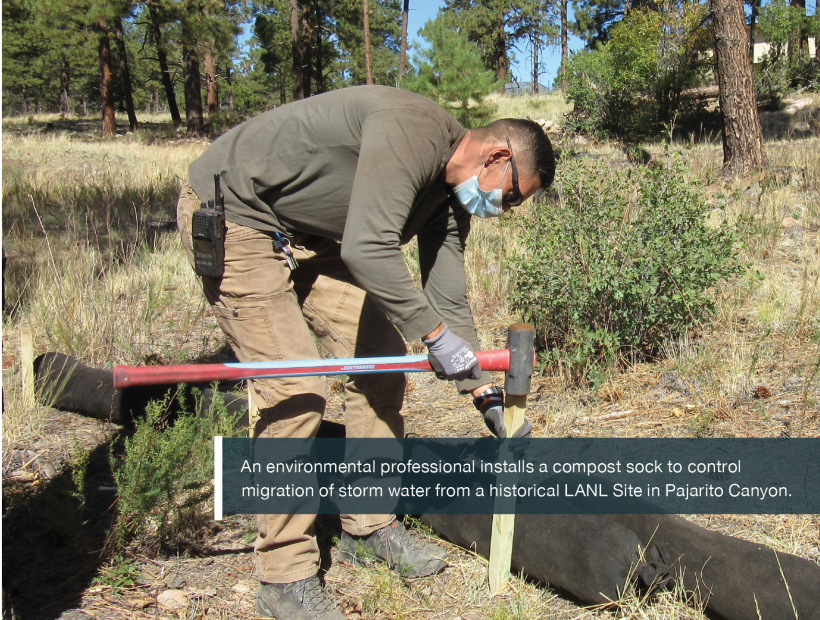 An environmental professional installs a compost sock to control migration of storm water from a historical LANL Site in Pajarito Canyon.
