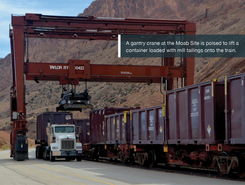 A gantry crane at the Moab Site is poised to lift a container loaded with mill tailings onto the train.