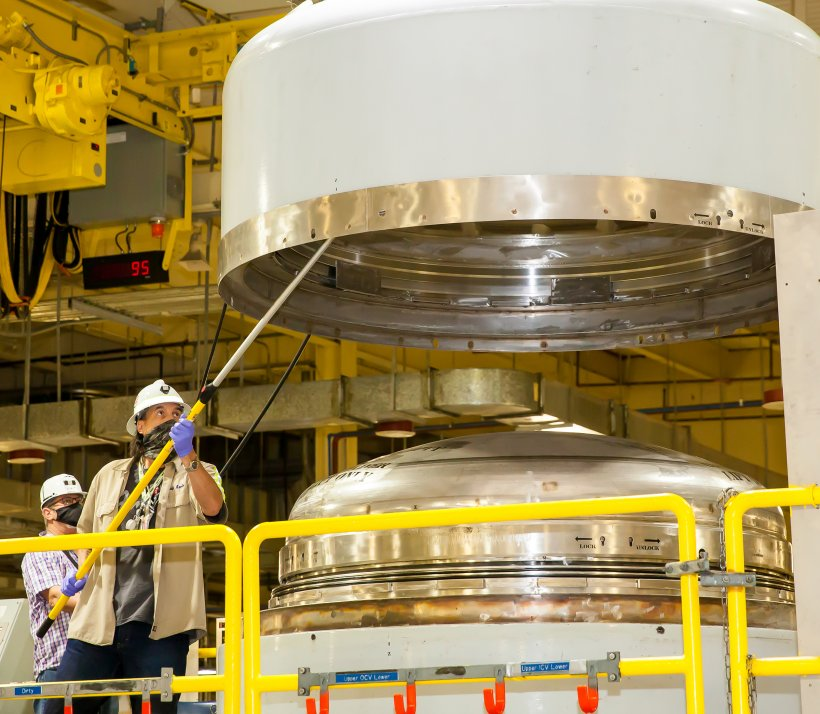 A radiological worker surveys the inside of a TRUPACT-II containment lid during waste handling operations at the Waste Isolation Pilot Plant in New Mexico.