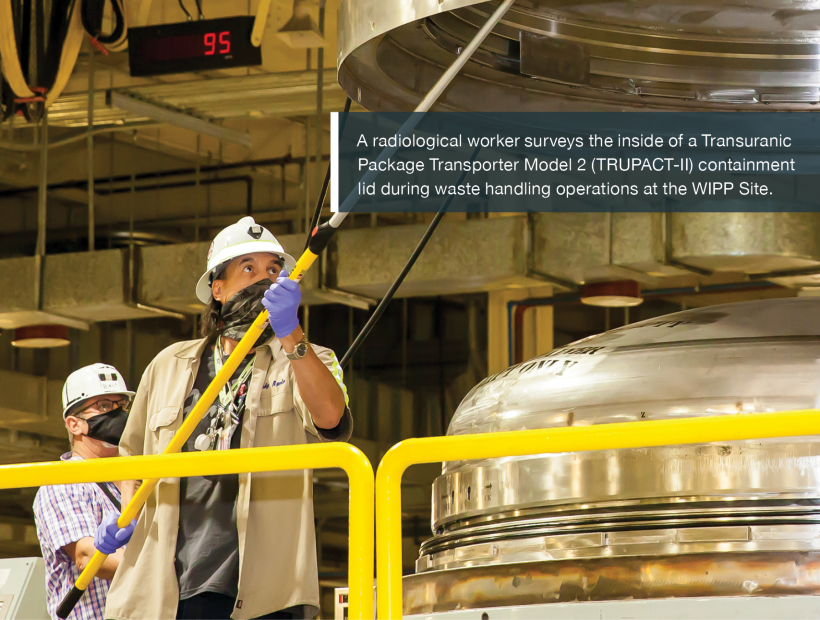 A radiological worker surveys the inside of a Transuranic Package Transporter Model 2 (TRUPACT-II) containment lid during waste handling operations at the WIPP Site.