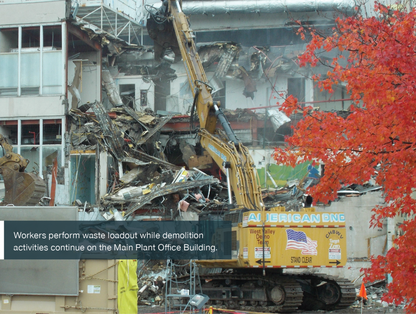 Workers perform waste loadout while demolition activities continue on the Main Plant Office Building.