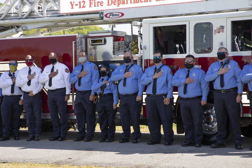 Y-12 firefighters hold their hands over their hearts during the ceremony.
