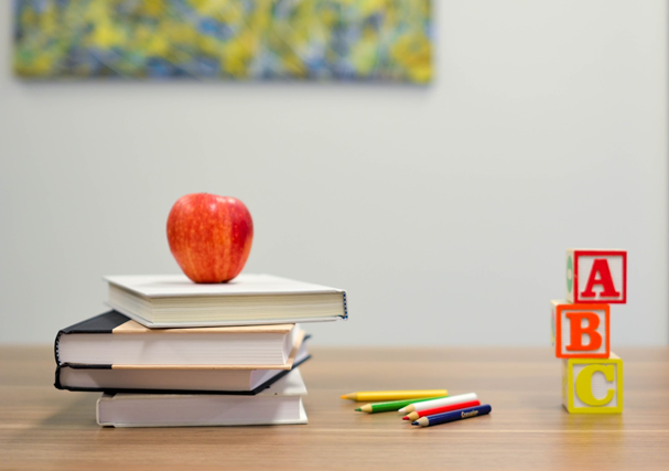 """Photo of stacks of books on a table, with an apple on top, next to a few assorted-color pencils, and three building blocks with """"A,"""" """"B"""" and """"C"""" on them."""