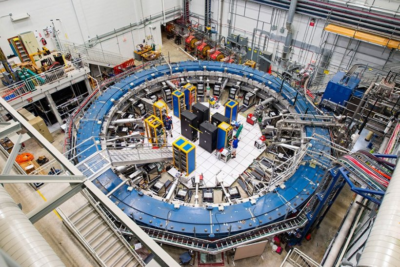 A blue mechanical ring surrounded by machinery and scientific equipment.