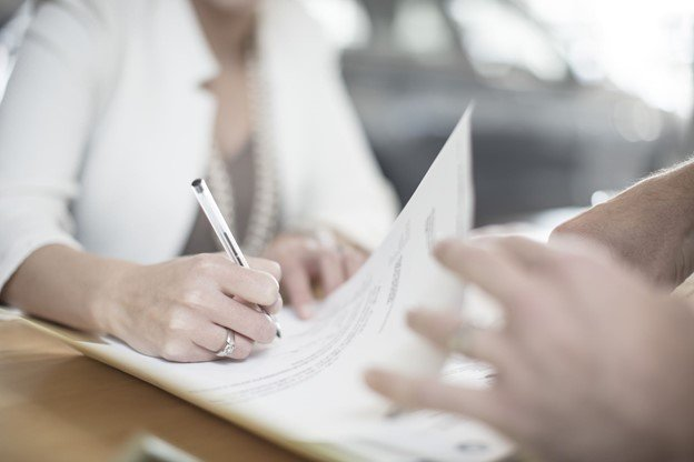 A shot of one person signing a document and another holding the paper.
