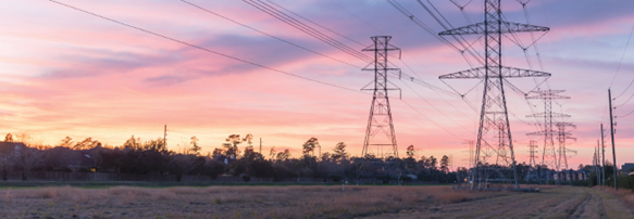 Image of power lines silhouetted by a sunset sky.