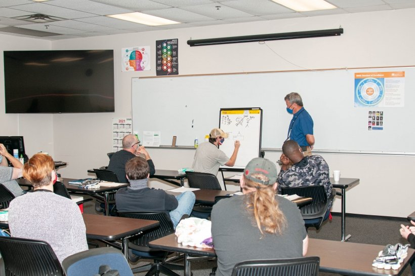 Production Operator Apprentice Brandon Richardson participates in a dynamic learning activity at the human performance improvement lab at the Savannah River Site. Conduct of Operations Program Manager Daryl Smoldt is to the right of Richardson.