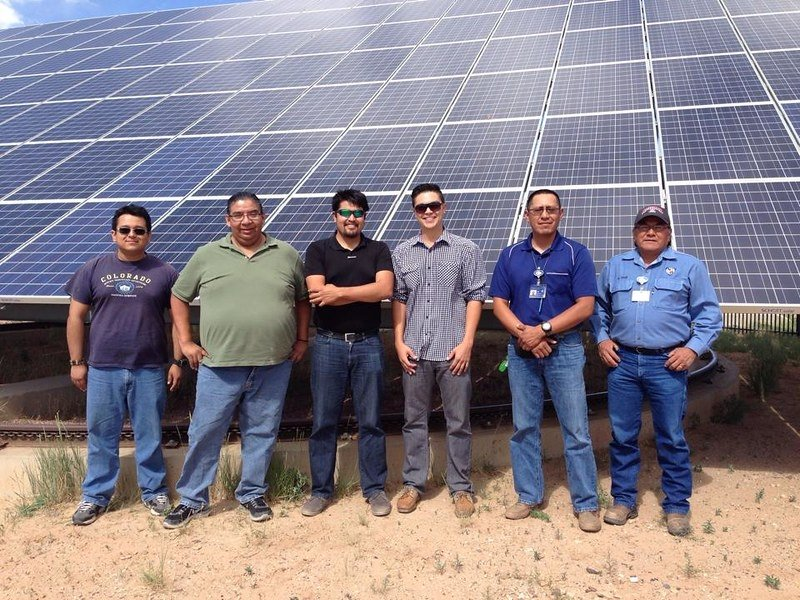Interns stand in front of solar panel.