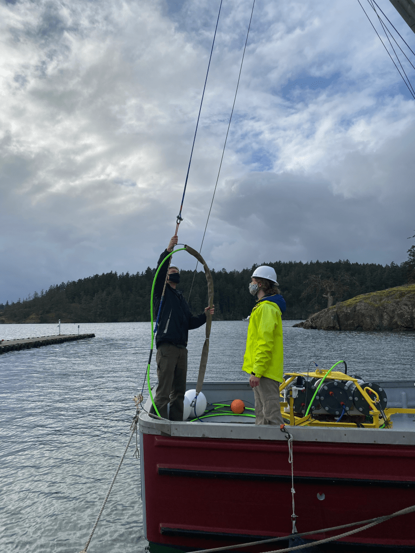 Photo of two men on a boat preparing an acoustic buoy unit for deployment.