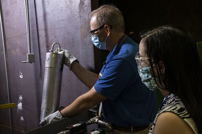 Savannah River Nuclear Solutions and Savannah River National Laboratory (SRNL) developed a mock-up to test underwater cameras and accompanying long-handled tools to perform examinations of spent nuclear fuel bundles in a basin at the Savannah River Site. Here SRNL employee Kevin Counts holds a small section of a test bundle against an underwater camera as SRNL employee Lisa Ward looks on.