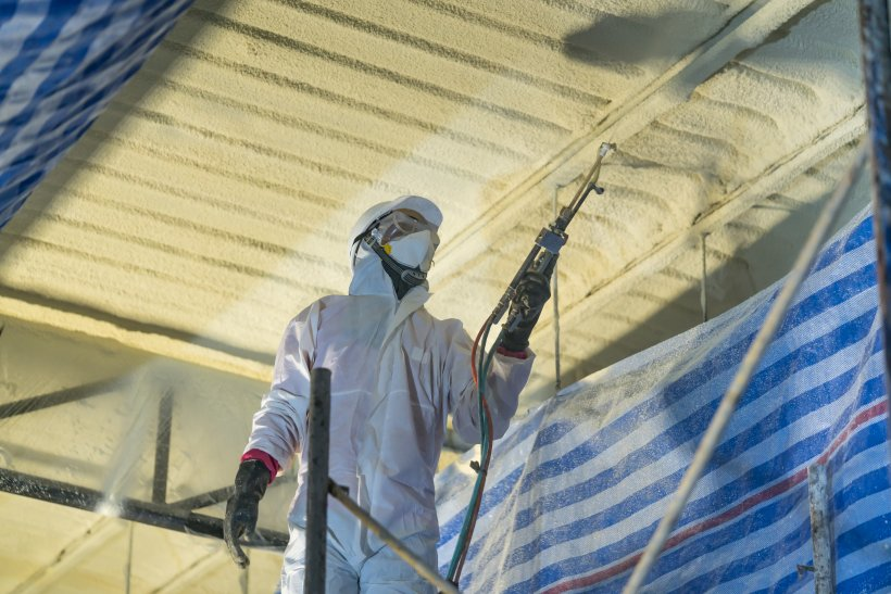 An HVAC worker wearing a protective suit and blowing in insulation for the ceiling of a building.