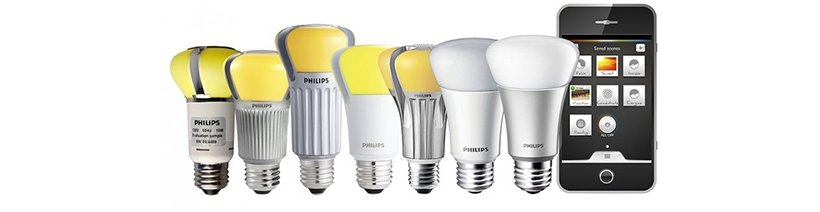 seven LED light bulbs and a smartphone, lined up in a row