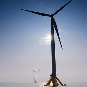 Offshore wind turbines at sea with sun shining.