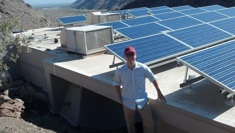Tommy Jones standing in front of PV panels.
