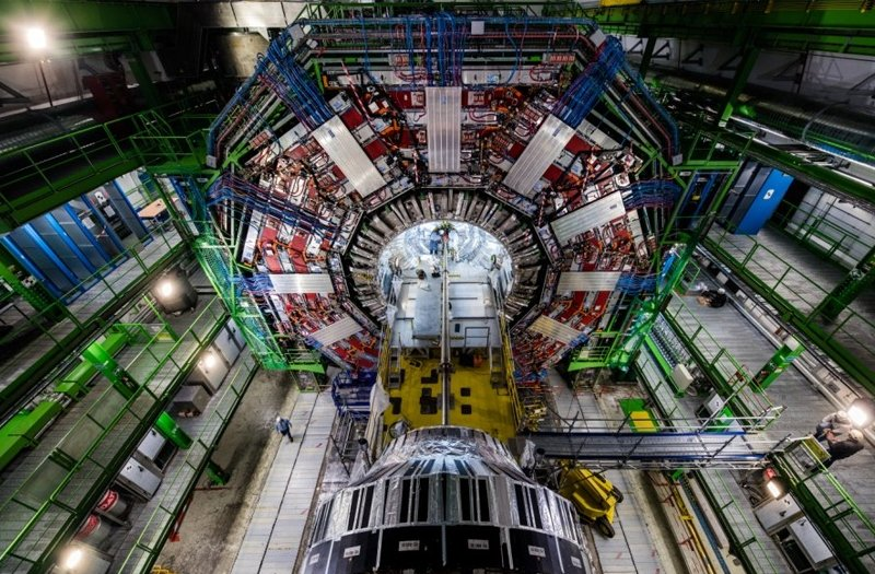 Aerial view of the Large Hadron Collider, a huge machine with a giant ring surrounded by balconies and scaffolding