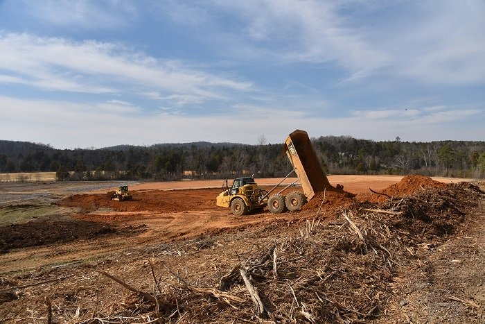 Crews used more than 2,000 truckloads of topsoil to recontour a portion of the former Powerhouse Area at Oak Ridge. UCOR employees identified an innovative approach to avoid costs and enhance efficiency by grading down a nearby ridge to obtain soil for the work.