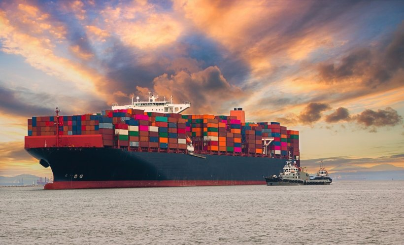 Cargo ship loaded up with shipping containers on the water with a smaller ship in font of it.