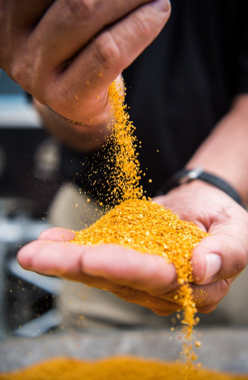 Close up of someone pouring corn from one hand to another.