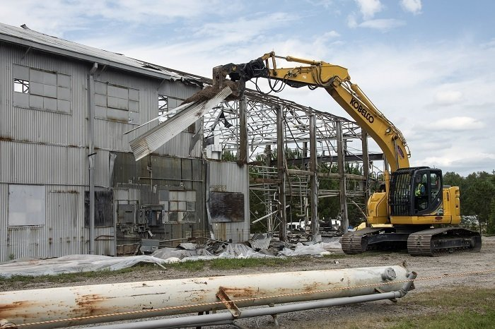 Workers demolish a section of the metal roof over the Ford Building at the Savannah River Site. At the height of the Cold War, the facility was used to test components used in five nuclear reactors at the site.