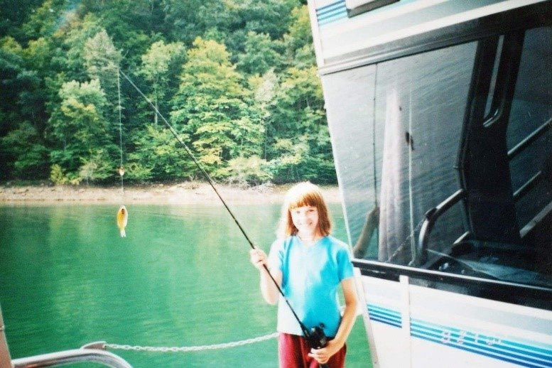 A girl smiling with a fishing pole.