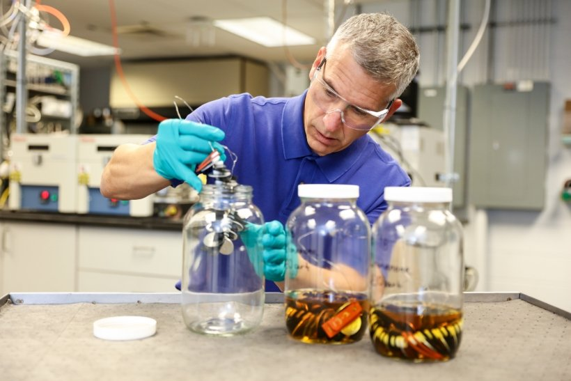 Scientist placing a mechanism into one of three clear jars.