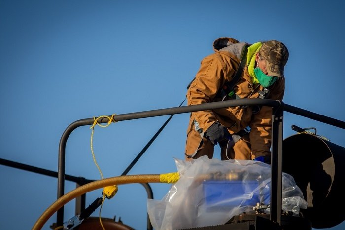 Paducah Site worker Cayce King connects a hose to a rail car to drain oil from the C-531 switchyard. Each rail car can hold approximately 25,000 gallons of oil.