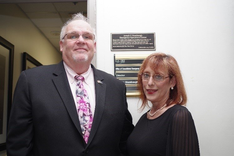 Joe Stambaugh with his wife, Lisa, proudly posing in front of the CEOC dedication plaque