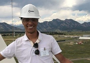 Headshot of a male smiling with a hard hat on.