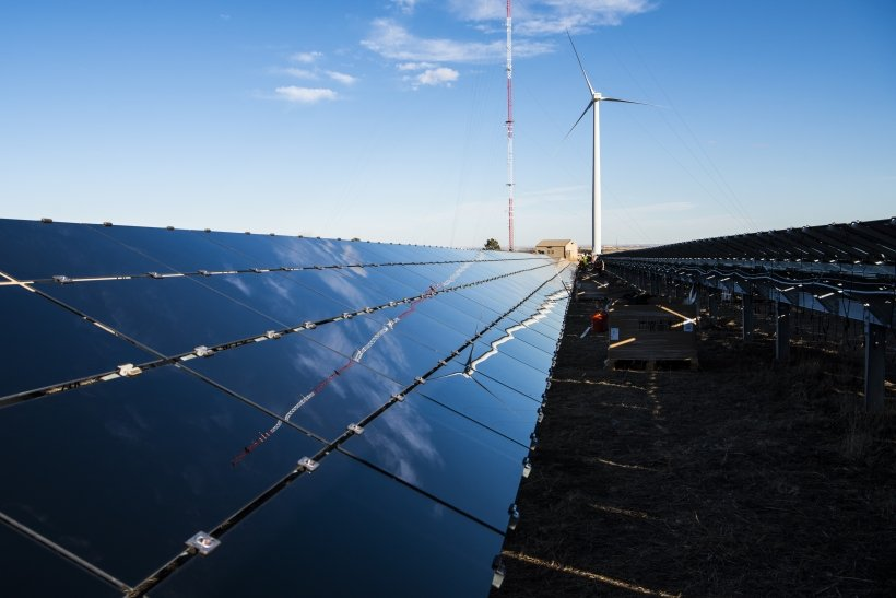 Photo of wind turbine next to a solar panel array, with images of the wind turbine and blue sky reflecting off the solar panels.