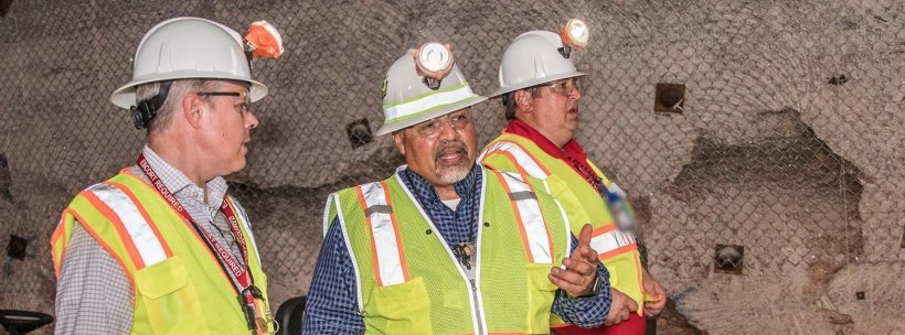 """Ed Garza, center, assistant manager at EM's Carlsbad Field Office (CBFO), explains current operations in the Waste Isolation Pilot Plant underground to EM Acting Assistant Secretary William """"Ike"""" White. CBFO Manager Reinhard Knerr is behind Garza."""